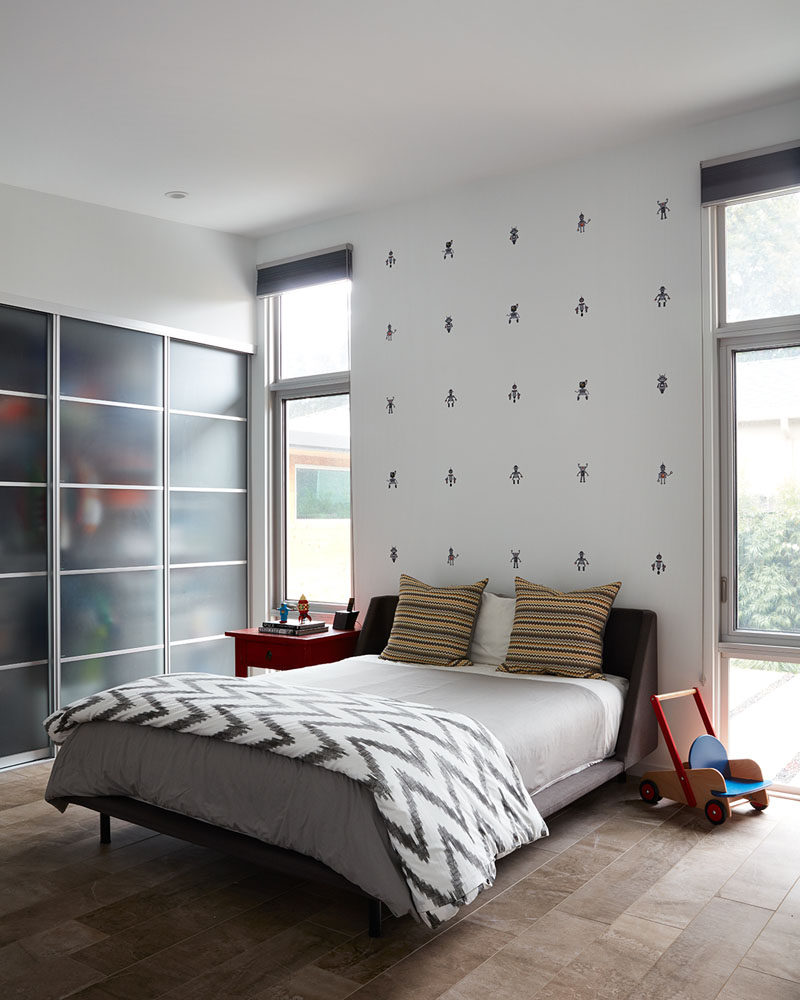 This modern bedroom is designed so that the bed sits between two windows and against a wall with decorative motifs. The closet is accessed by a set of sliding doors.