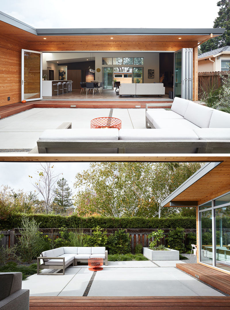 This modern house has a folding wall system that allows the interior of the home to open up to the outside courtyards, designed by landscaping company, Growsgreen. The patio has a comfortable outdoor corner sofa with white cushions that match the white walls of the interior of the home and a fire pit for cooler nights.