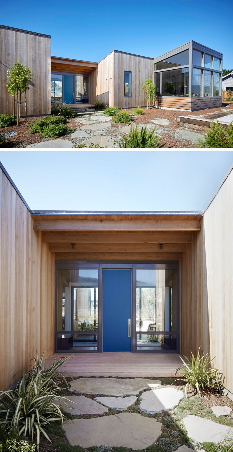 Surrounded by light wood cladding and large windows revealing the interior of the house, the front door provides a nice blue addition to the exterior of this modern home.