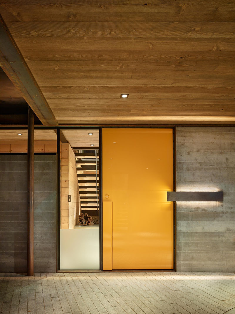 The vibrant yellow door of this industrious home is placed beside a window, giving a glimpse of the interior of this modern house.
