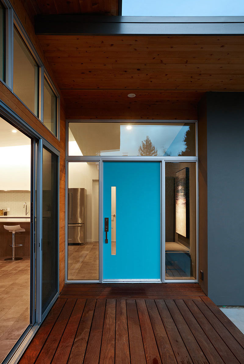 The electric blue door of this house is framed by glass windows, making the entrance of this modern home look larger
