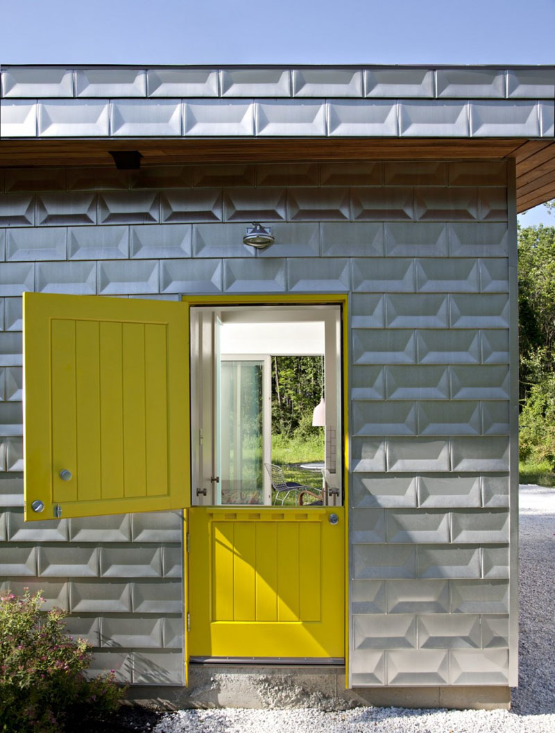 The cottage-style yellow front door that can be opened two ways, bounces color off the brick-like, matte aluminium exterior of this modern house.