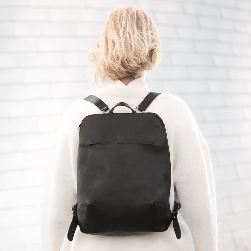 Made from vegetable tanned leather, this black modern backpack is simplistic yet completely practical for everyday life.