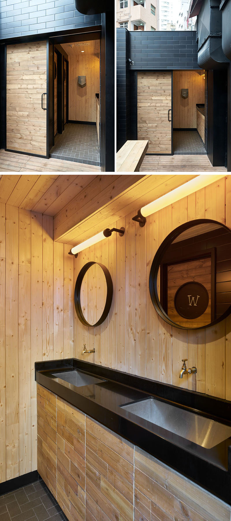 This modern coffee shop has a set of minimally decorated washrooms that stand out on a black wall with wood sliding doors. The interior is full of light wood, and the vanity features a black countertop with undermount sinks, and hanging above are two black framed circular mirrors.