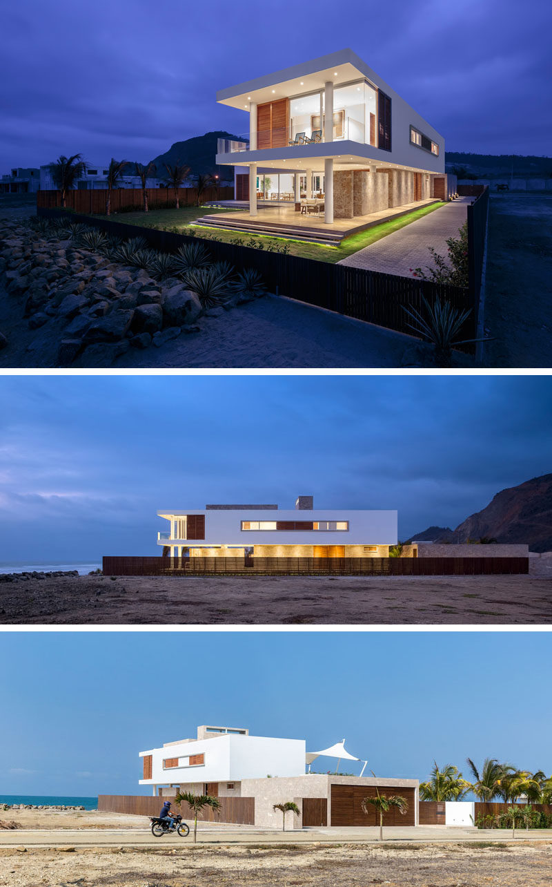 The exterior of this modern beach house naturally suits the landscape around it and has a material palette of white, wood, and stone. At night the residence lights up from all angles creating an ethereal effect.
