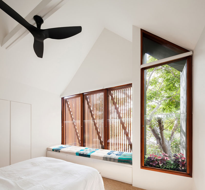 This mostly white modern bedroom has wood window frames and a built-in window seat with storage and an upholstered cushion. A small window box adds a touch of nature to the room.