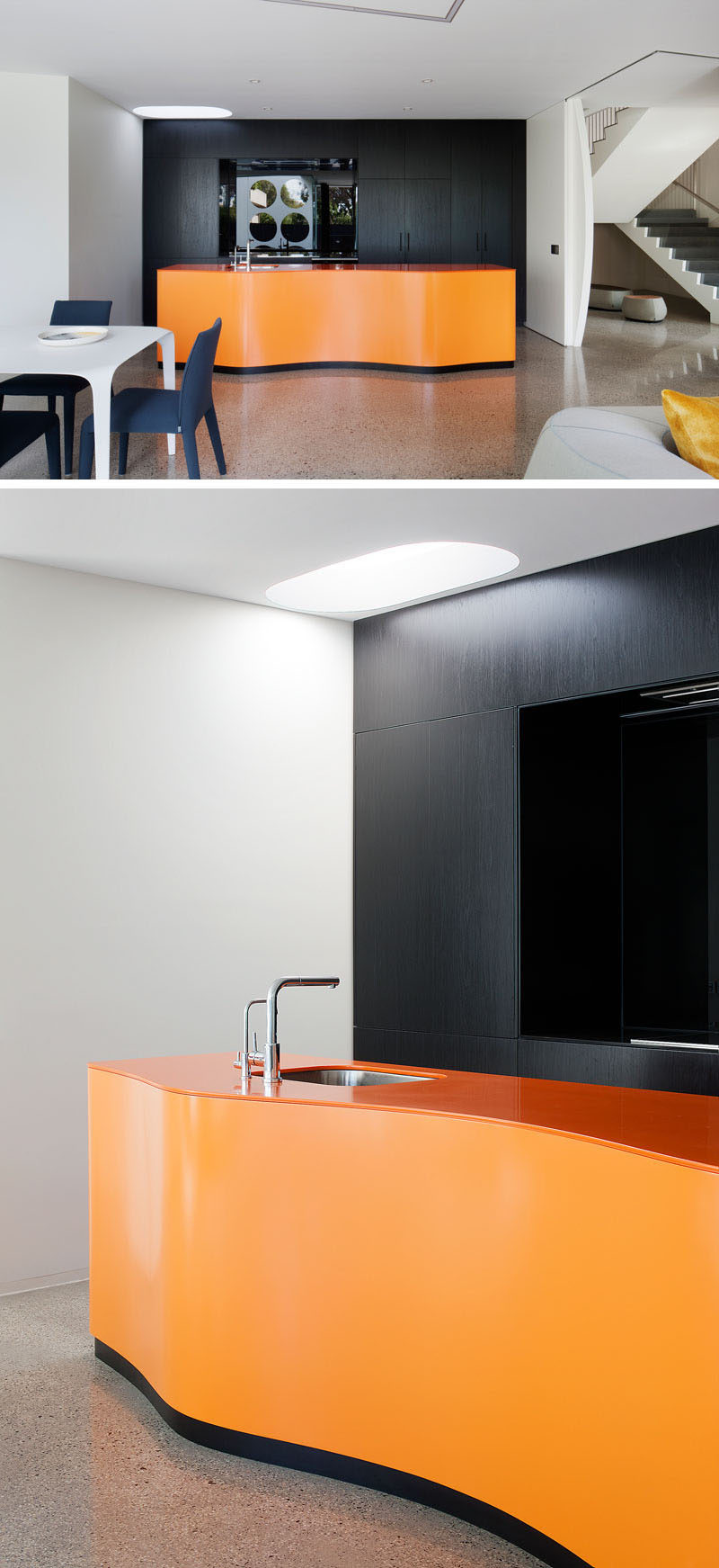 This boldly colored modern kitchen has a curved orange island, while the black cabinets, with an integrated fridge, provide a strong contrast and help to make the color of the island 'pop'. The flooring throughout the house is a hand-crafted polished concrete floor.