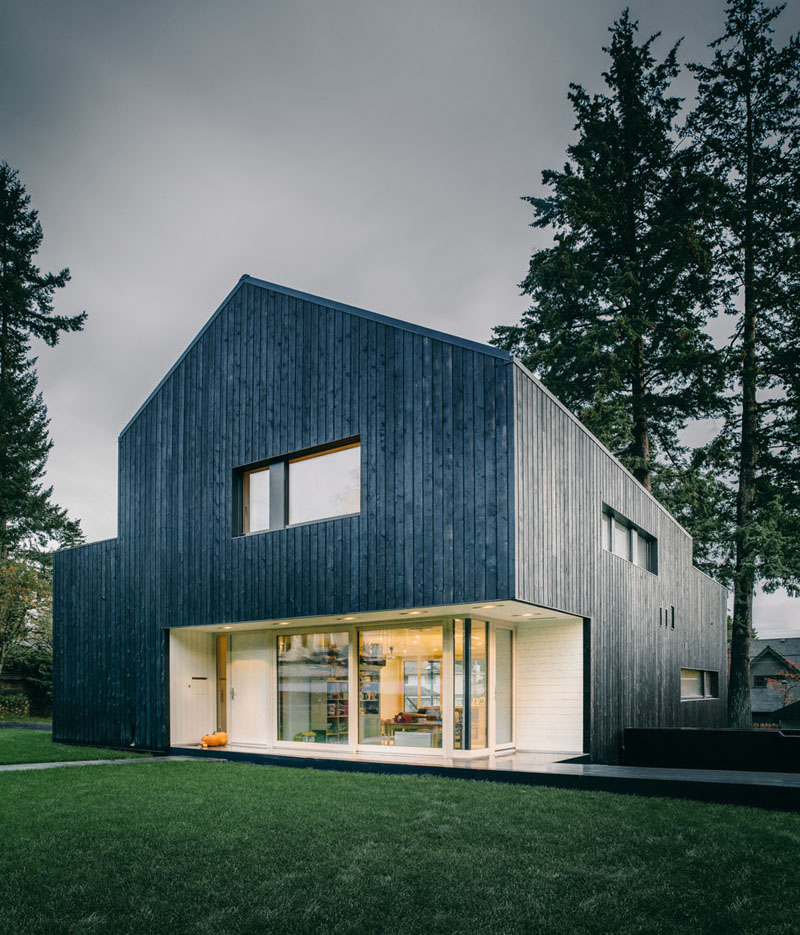 burnt blackened wood panels cover the entire exterior of this modern forest home