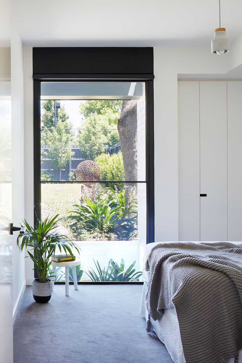 This modern bedroom features a tall black framed window that highlights the sculpture in the garden.