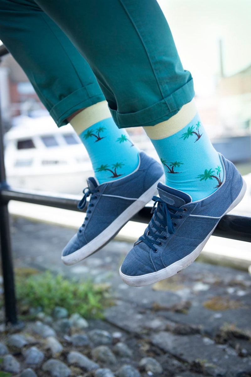 These modern neon blue socks with palm trees reflect a laid back lifestyle.