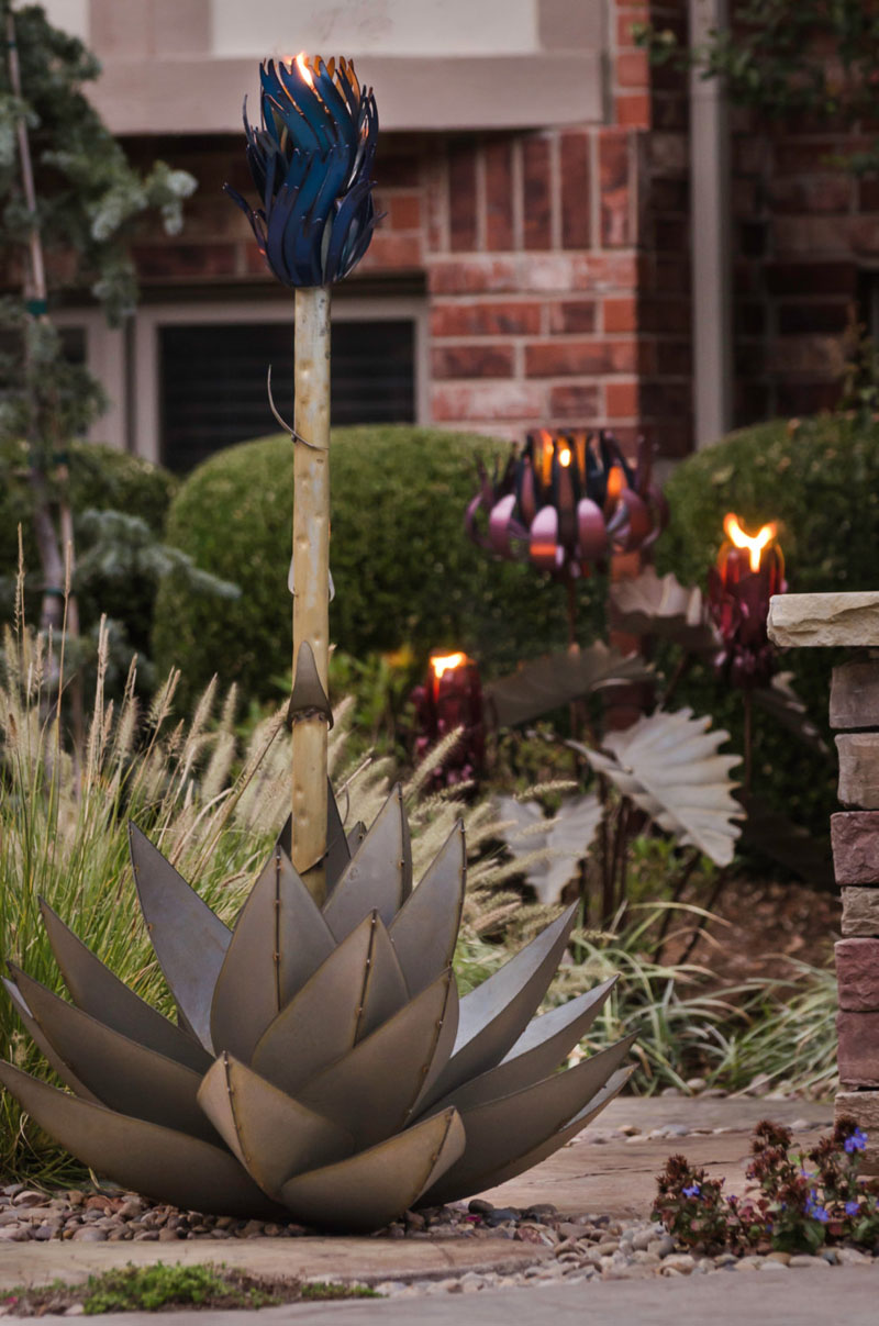 This modern blue agave torch is made from steel and lights up the backyard.