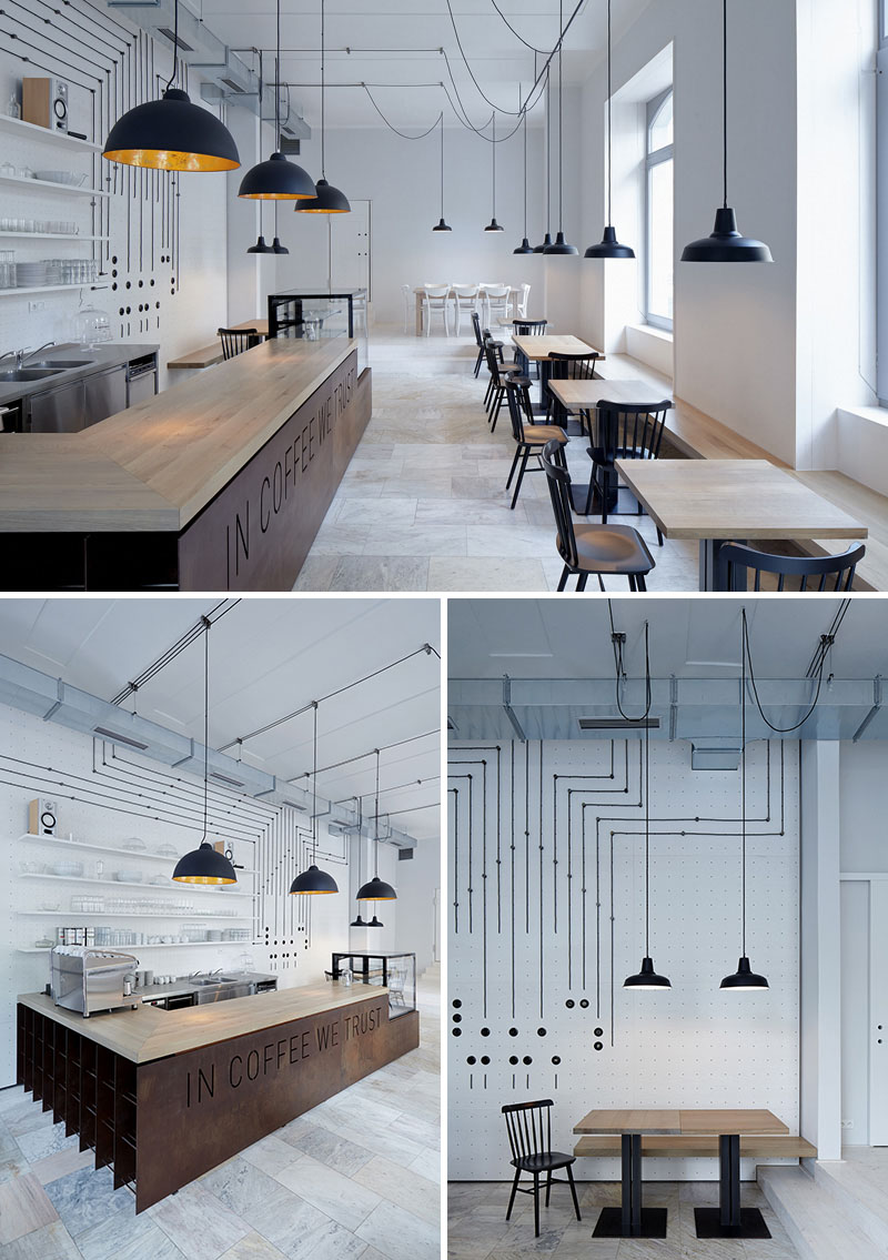 With white perforated plywood, a grid is created to connect the various components of this modern cafe, including the matte black pendant lights