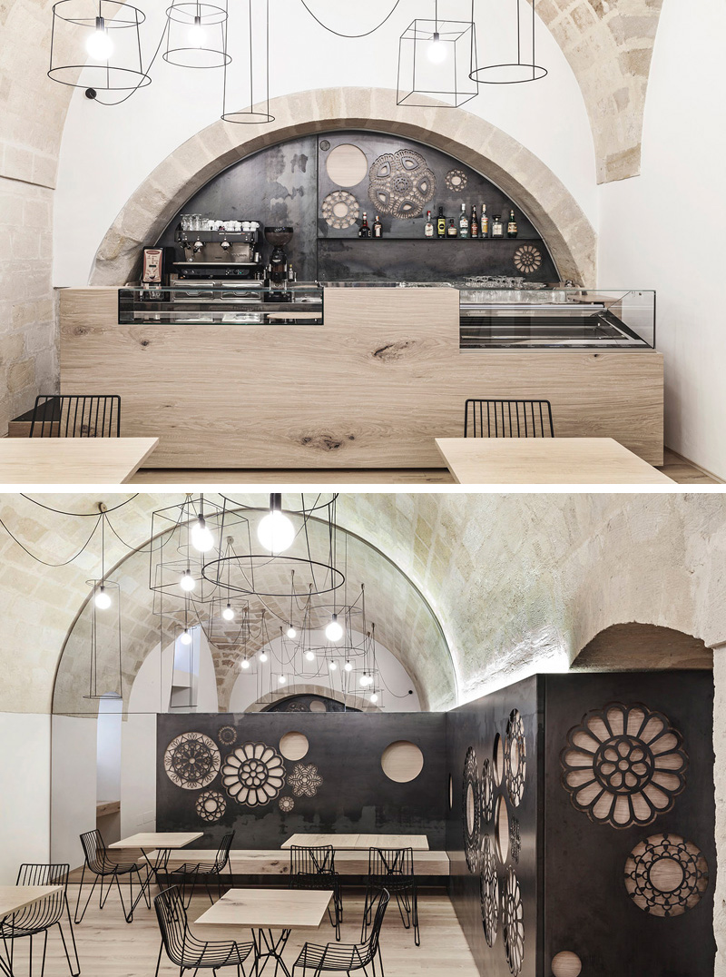 This cafe features minimalist design and steel panels on the walls with a variety of cut out motifs to create a modern look in the old building.