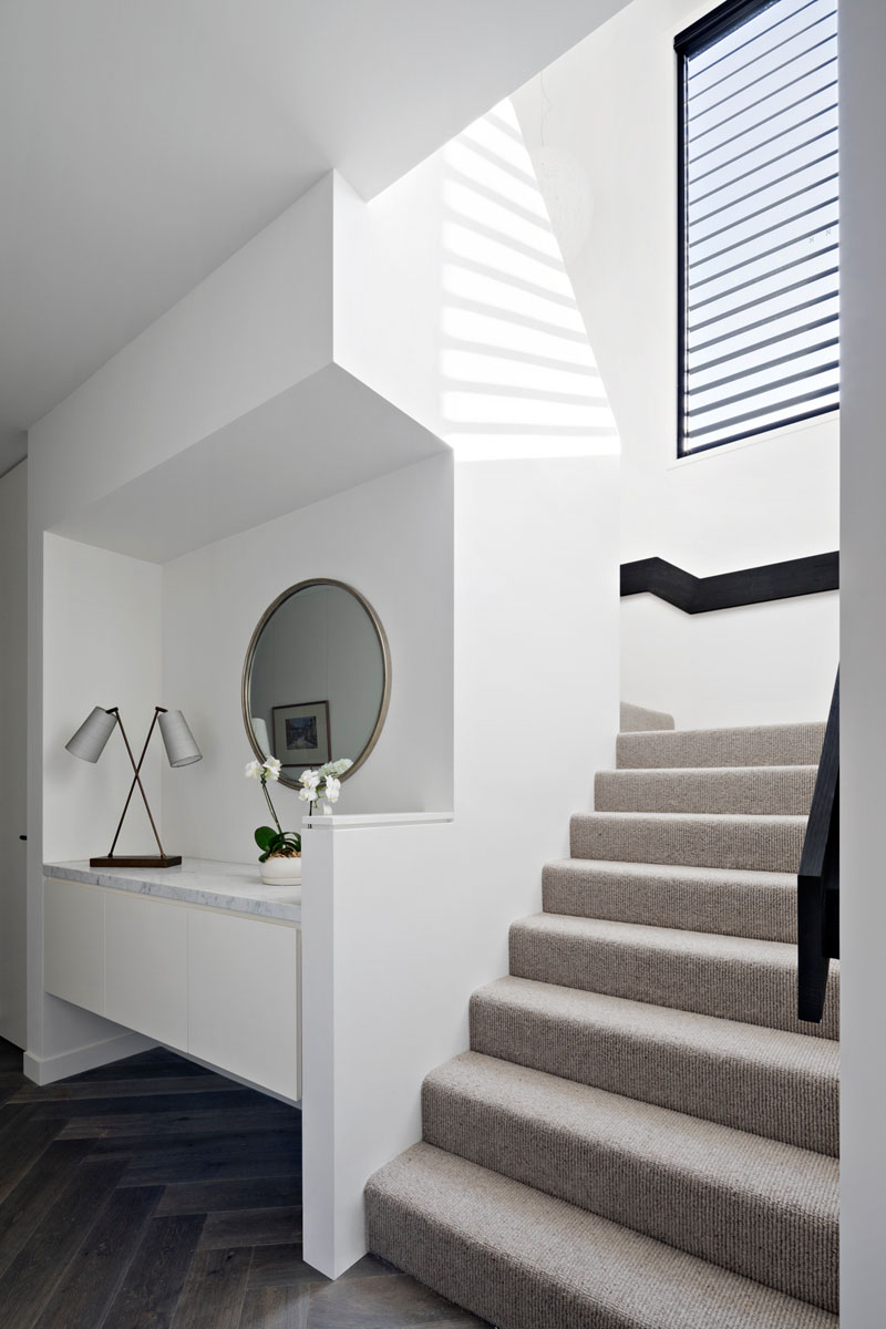 This modern hallway has a floating built-in cabinet, with a light colored carpeted staircase and a black railing that leads to the upper floor, with a matching black window frame.