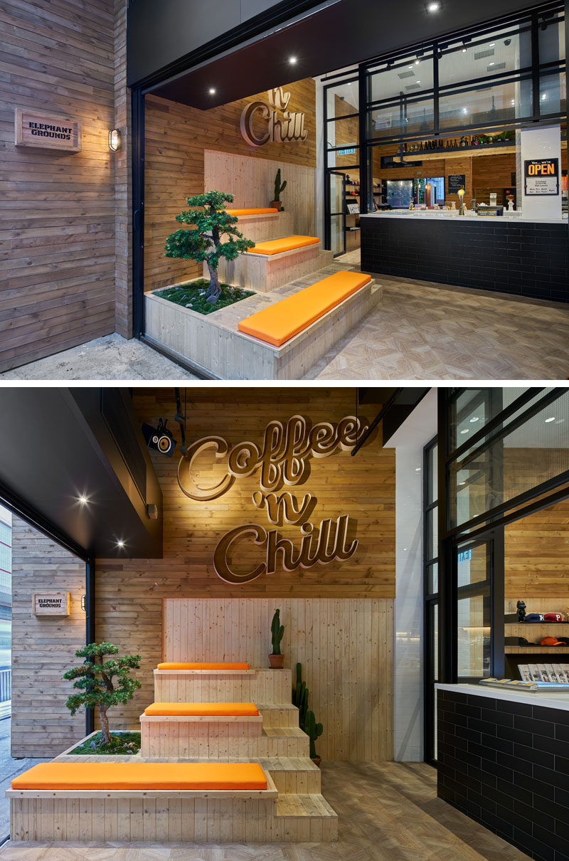"This modern coffee shop has custom designed wood tiered seating with orange cushions that sits below a lighted three dimensional wood sign that reads, ""Coffee 'n Chill."" A green bonsai and a few cacti add a touch of nature color to the seating arrangement in this indoor-outdoor anteroom."