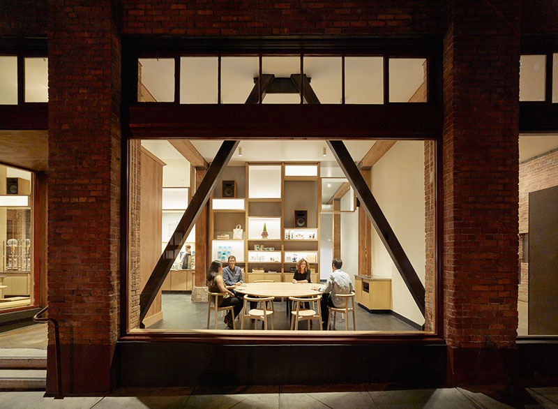 The large framed windows provide a glimpse of the minimally decorated interior of this modern cafe. Large wood seating arrangements allow for groups of people to stop by and work, or catch up with one another.