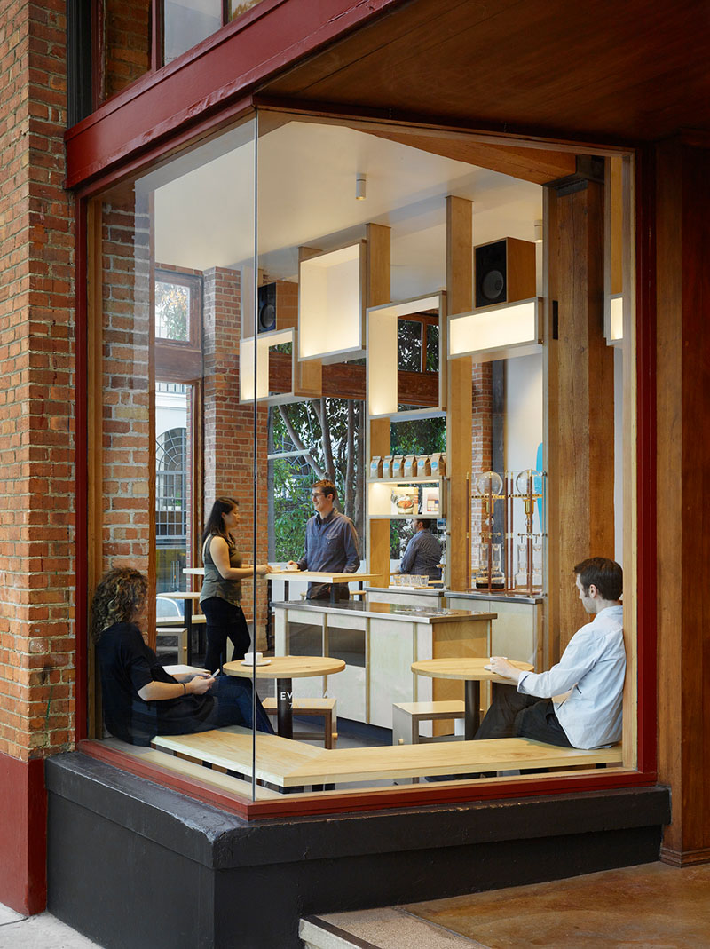 Banquet style, solid ash wood seating is utilised in the corner window of this modern cafe, providing extra space for patrons that allows them to look outside while others look in.