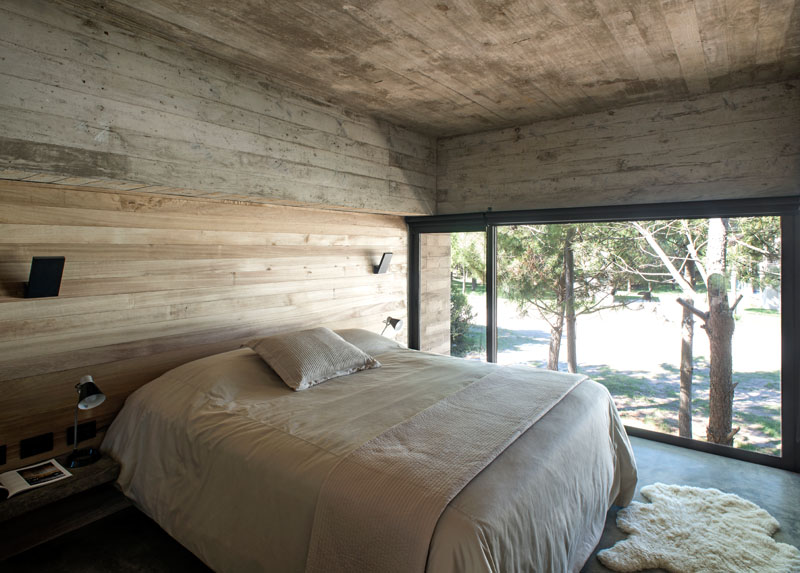 This modern, minimally decorated bedroom with a partial wood accent wall, has an elevated view of outside through the large framed window.