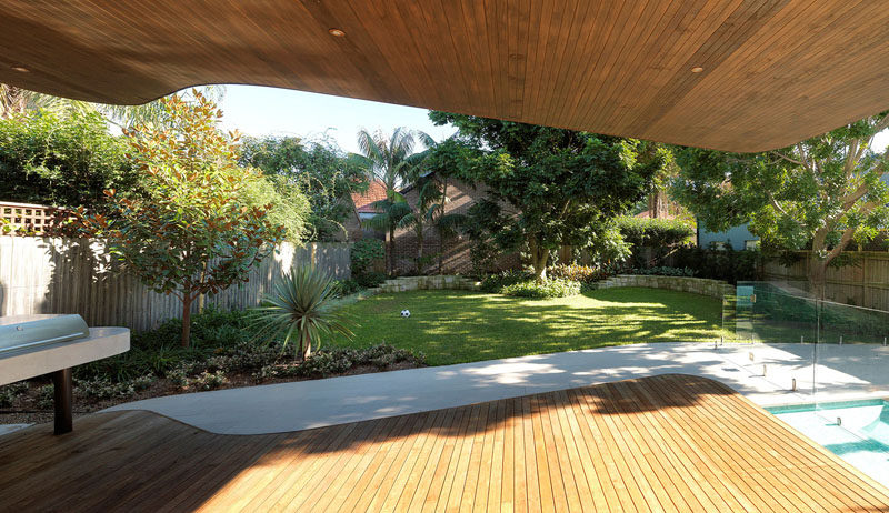 This modern house extension has a cantilever that provides shade to an outdoor space. A Blackbutt wood deck with a ceiling covered in Western Red Cedar has a bbq area off to the side, and a grassy backyard.