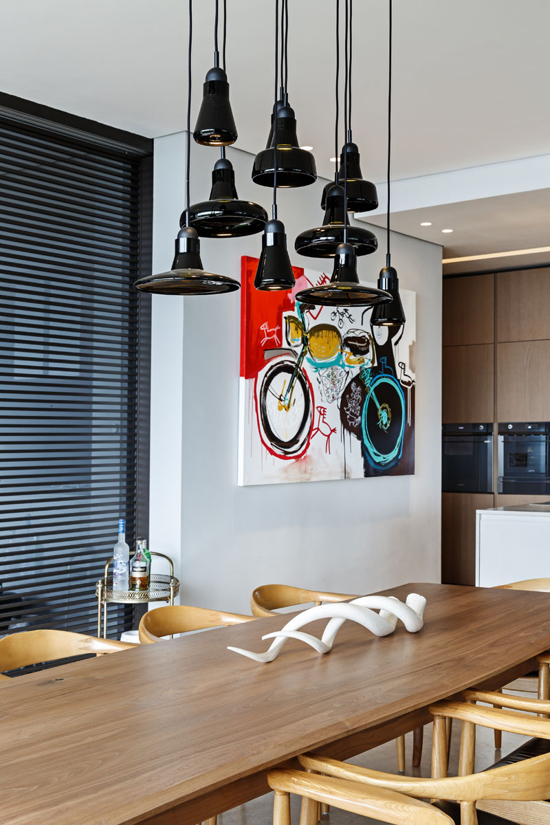 This modern dining area has a large wood dining table with light wood chairs, and glossy black pendant lights