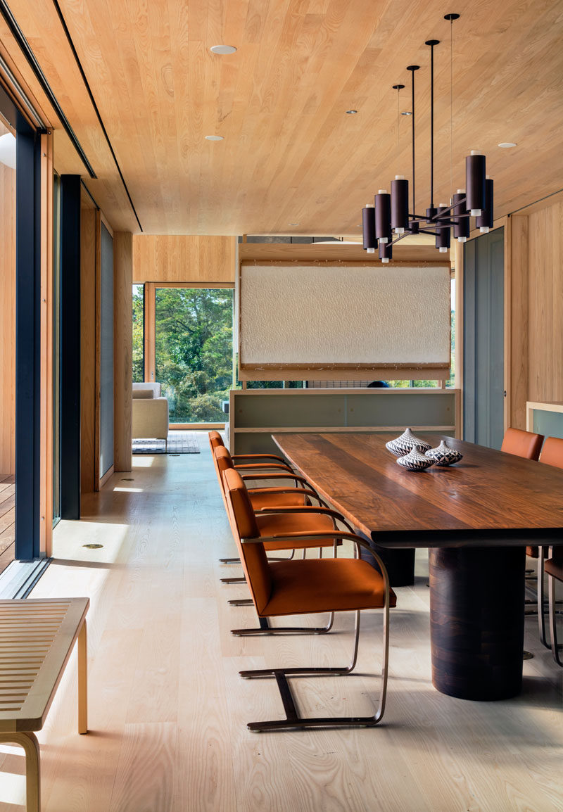 Upon entering this contemporary home, you walk into the main living and dining room. In the dining room, a large hand-carved wood table with a minimalist chandelier has plenty of room for family and guests.