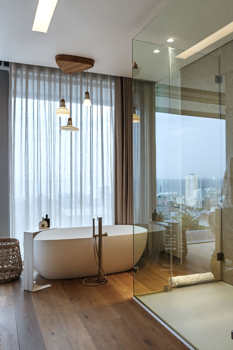 This modern master bathroom has a freestanding bath tub that sits beside large windows and a glass shower surround.
