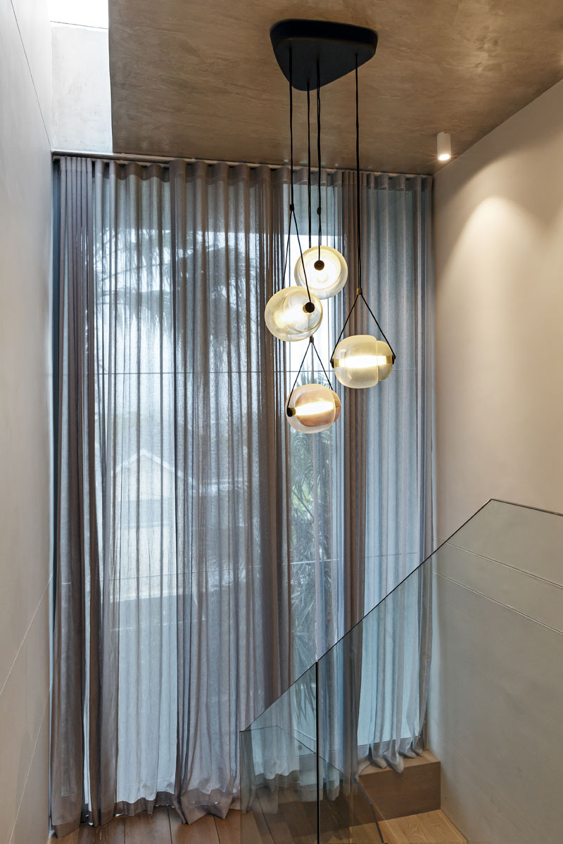 This modern stairwell has a glass hand railing staircase, a floor-to-ceiling window, and a set of large pendant lights.