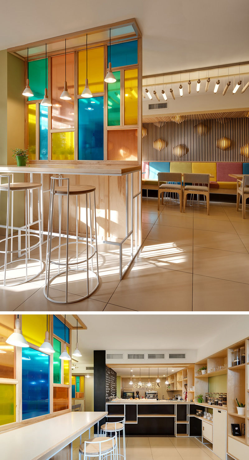 The colored glass paneled wall in this cafe-bakery creates a unique feature that matches the rest of the decor.