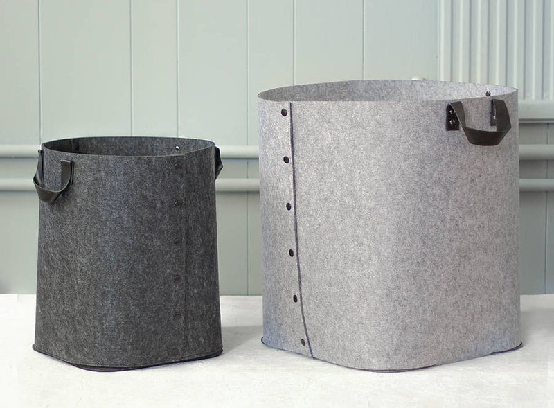 Made from reinforced felt, these grey laundry baskets have faux leather black handles. With the ability to collapse, these baskets are perfect for toting things around, and can be stored after use.