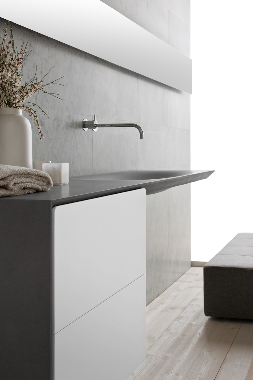 This modern grey stone sink is wall mounted, with large white drawers below to provide easy access to toiletries, and the slender chrome faucet is appealing to look at.