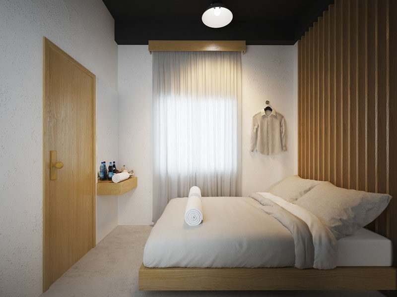 This private room in a modern hostel in Bangkok, has a wood slat accent wall that matches the wood door and bed frame.