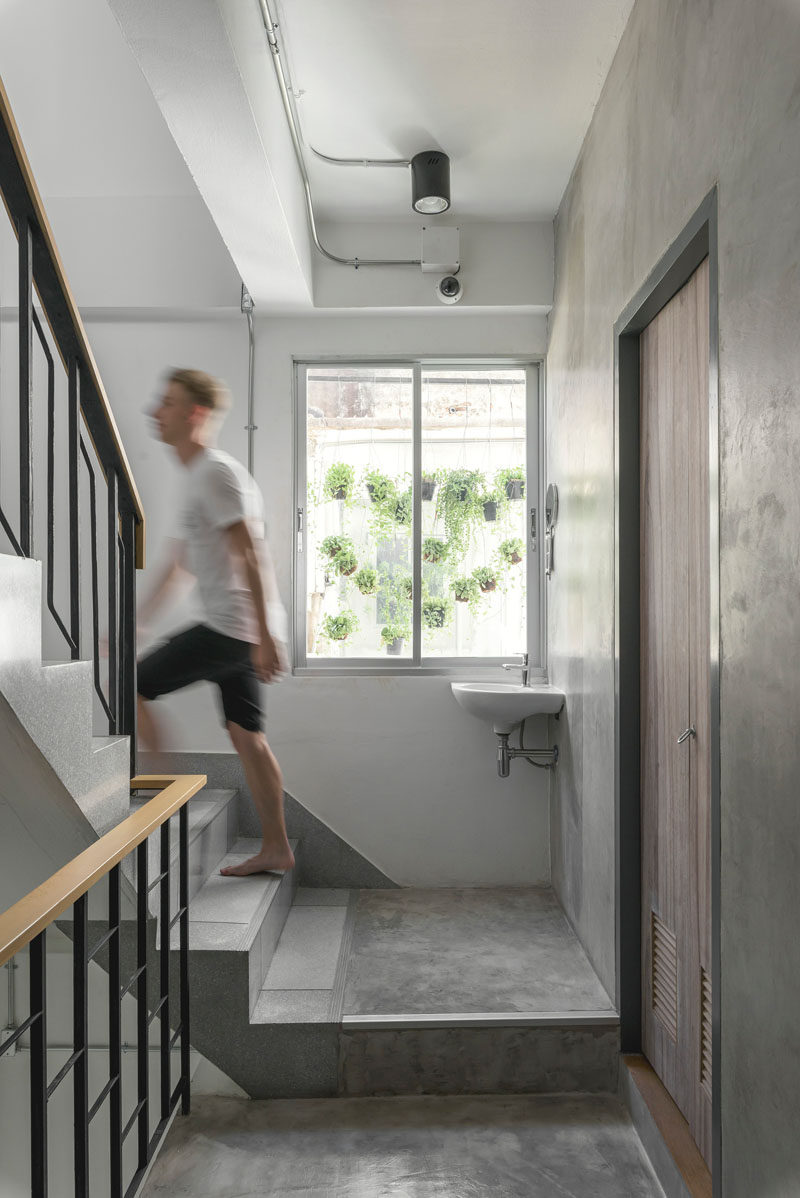 Concrete stairs with steel and wood railings lead you up to the sleeping areas of this modern hostel in Bangkok.