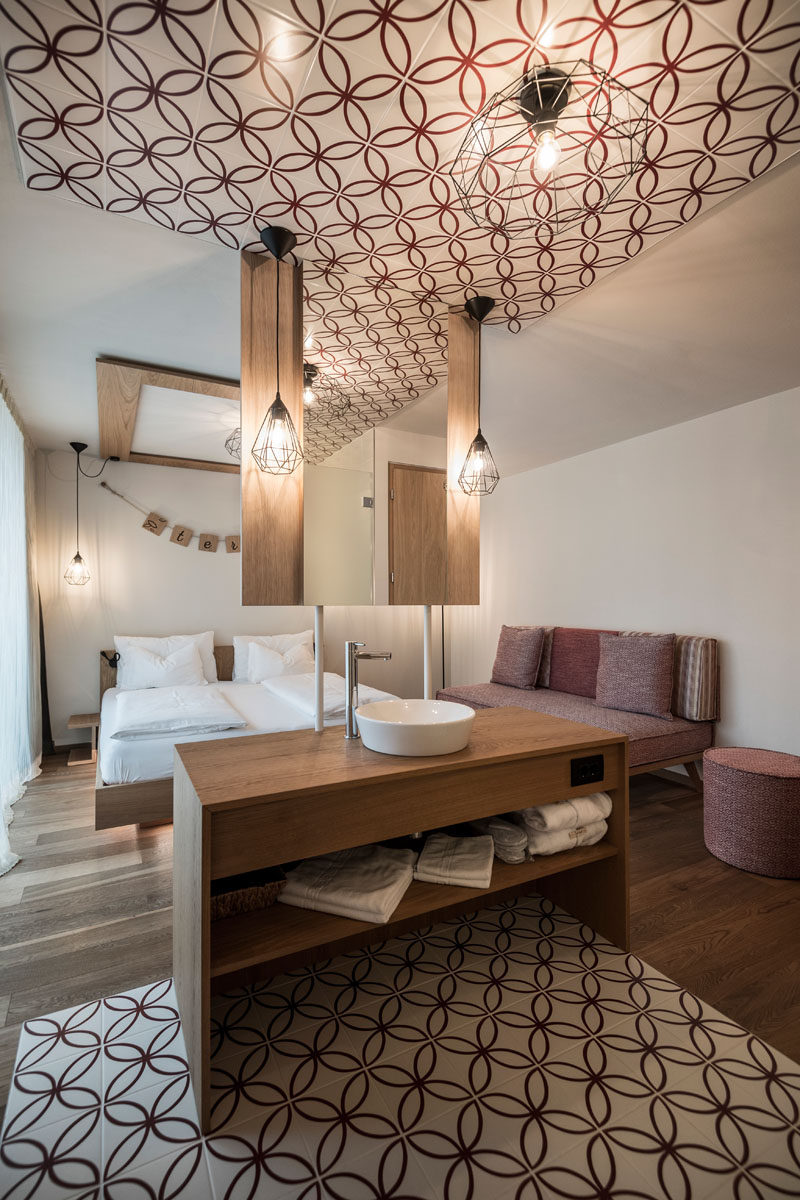 This modern hotel room has an open floor plan that's broken up by a wood vanity with a hanging mirror. The bathroom is defined by red and white patterned tiles that match the red sofa.
