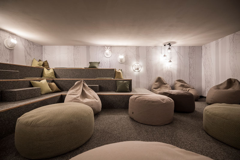 In this modern hotel, there's a relaxation room with floor to ceiling tree lined wallpaper, gray carpeted, and tiered benches. Animal light fixtures, and earth toned cushions and bean bags make this a perfect place to relax after adventuring in the wild.
