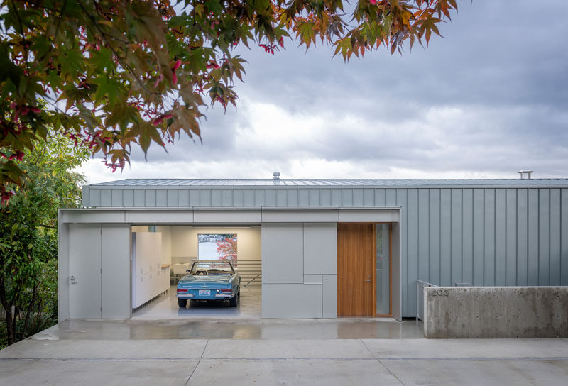 The exterior of this modern waterfront house has a shell of zinc and aluminum, with the garage and the wood front door being the only part of the house that you can see from the street.