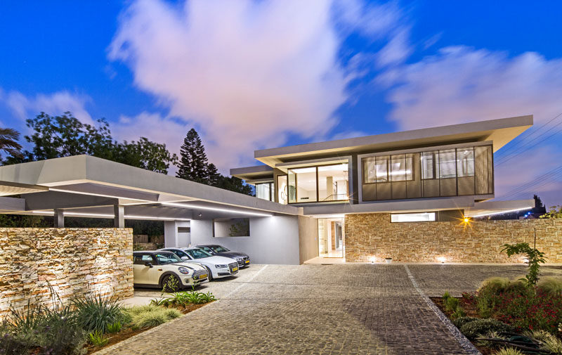 This modern house has a stone driveway that opens up to a parking area with carport on the left and visitor parking on the right.