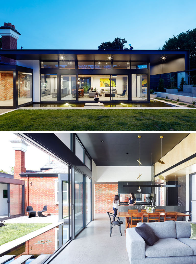 This modern house extension has a living room, dining area and a kitchen. You can see how the back brick wall of the original home is still visible in the new extension.