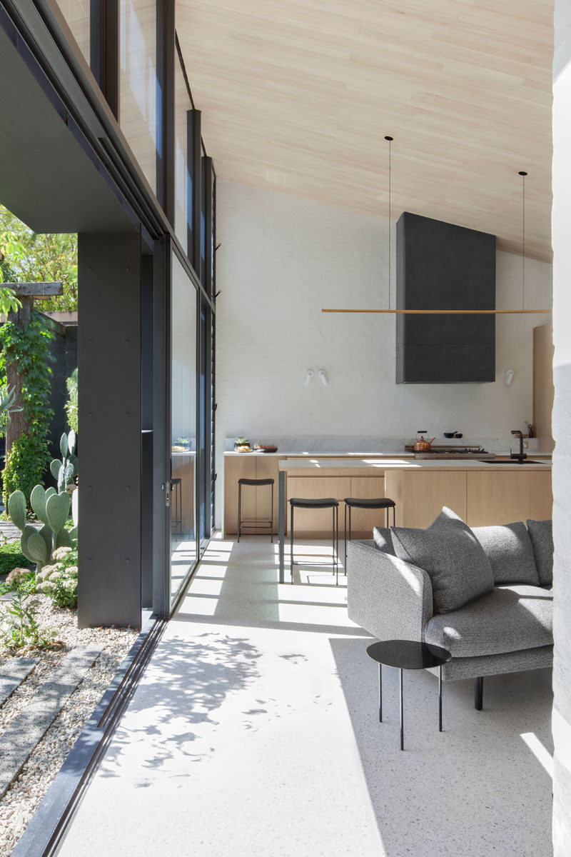 This modern house extension has large sliding glass doors that open to reveal the bright and airy interior with a slanted wood ceiling.
