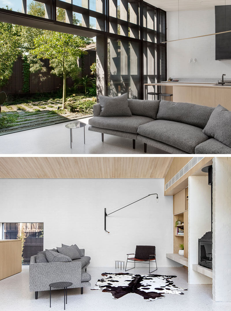 This modern living room that opens to a small sculptural backyard, has a grey curved couch that's positioned to view the black fireplace.