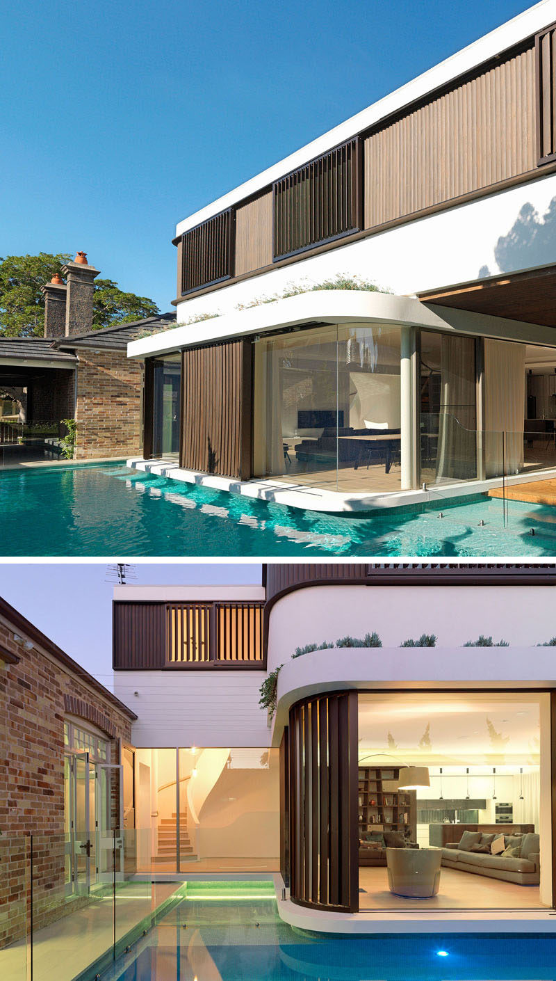 This modern two storey house extension has a wraparound swimming pool, and allows the water to be the main focus that holds the two distinct sections of the house together.