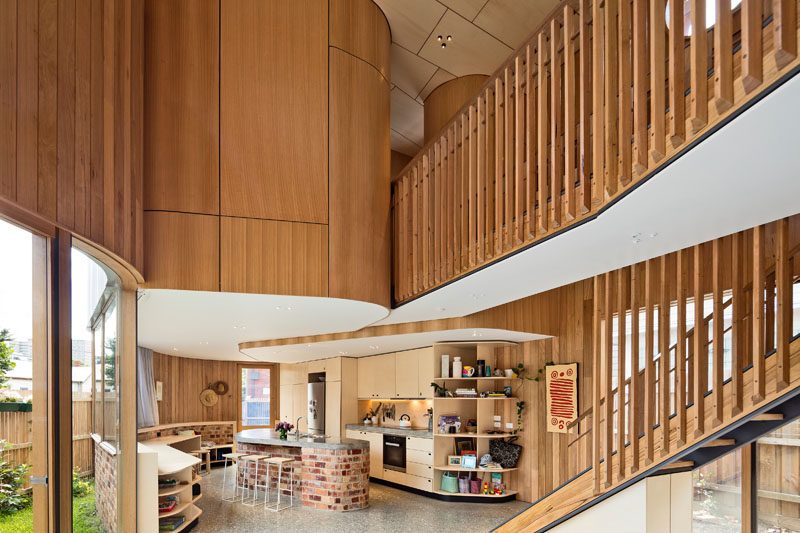 Inside this modern home, the curves continue with the walls and cabinetry. In the kitchen, the island is made from the same brick used on the exterior of the house, and curved open shelving creates additional storage without creating a hard and harsh edge.