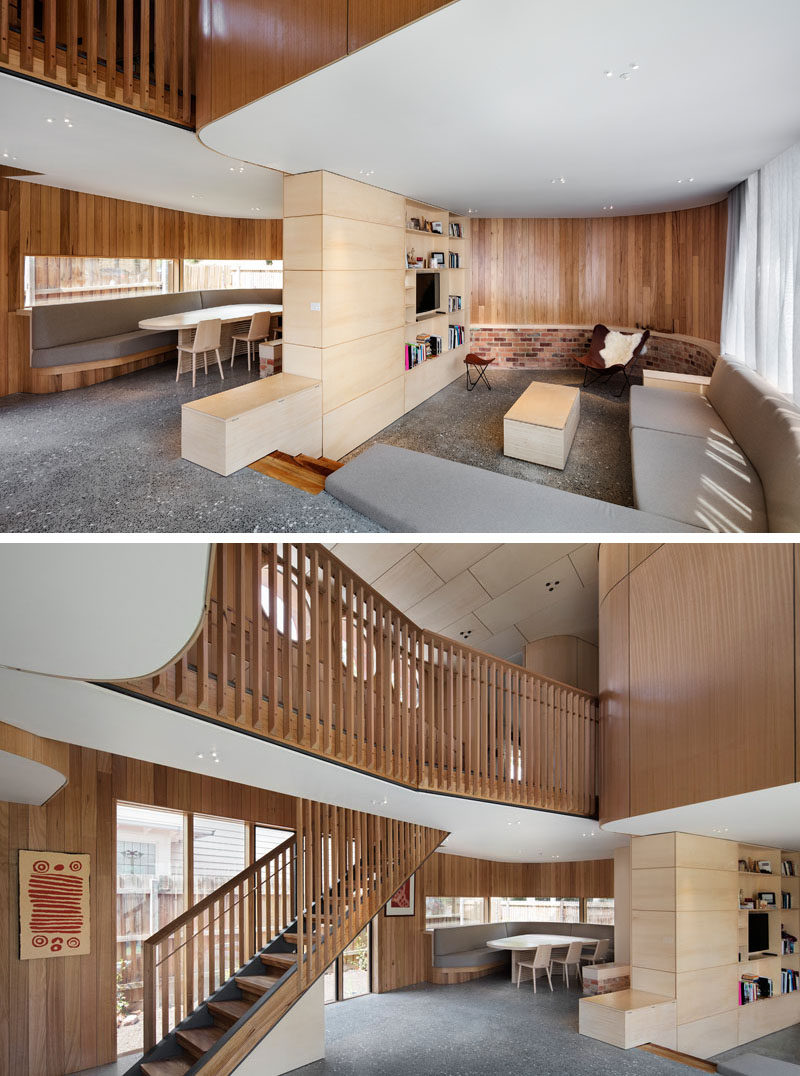 On the main floor of this house are the living and dining rooms. The living room steps down and a custom shelving unit separates it from the dining room. The dining room has bench seating that follows the curve of the house, and horizontal windows add light to the space.