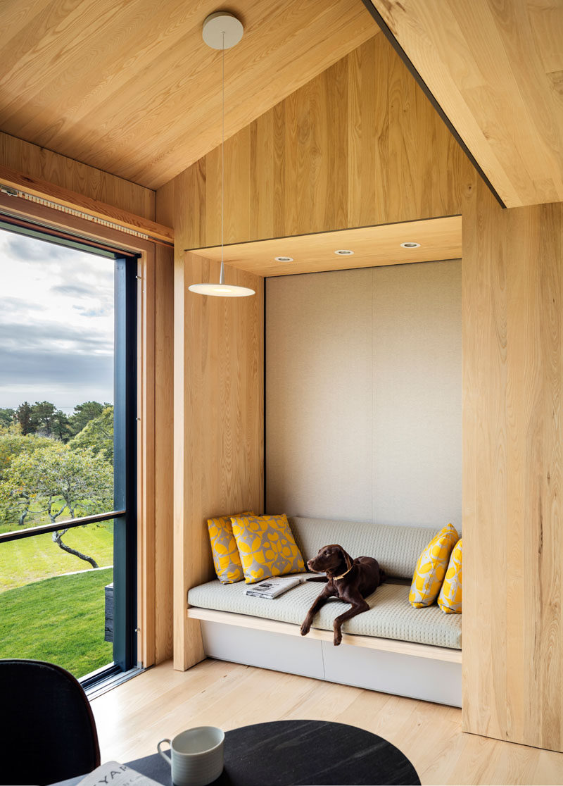 This built-in wood seating nook has a grey upholstery and yellow cushions for a pop of color.