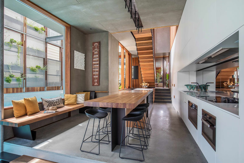In this open kitchen, there's a wood bench with cushions, and opposite there's a wall full of white kitchen cabinets, as well as the oven and stove. A mirrored backsplash helps to reflect light in the room and make it appear larger.