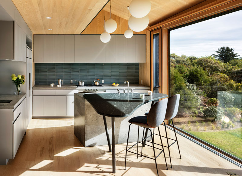 This modern kitchen has matte light grey cabinets and a curved island with space for seating. A large picture window perfectly frames the view.