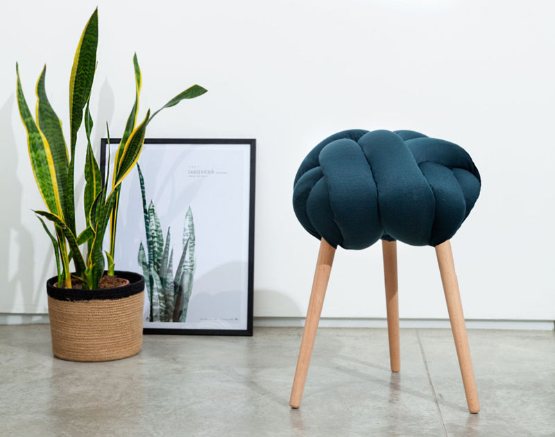 This modern stool is made from a solid fabric stuffed with foam filling, and is secured to Beech wood legs.