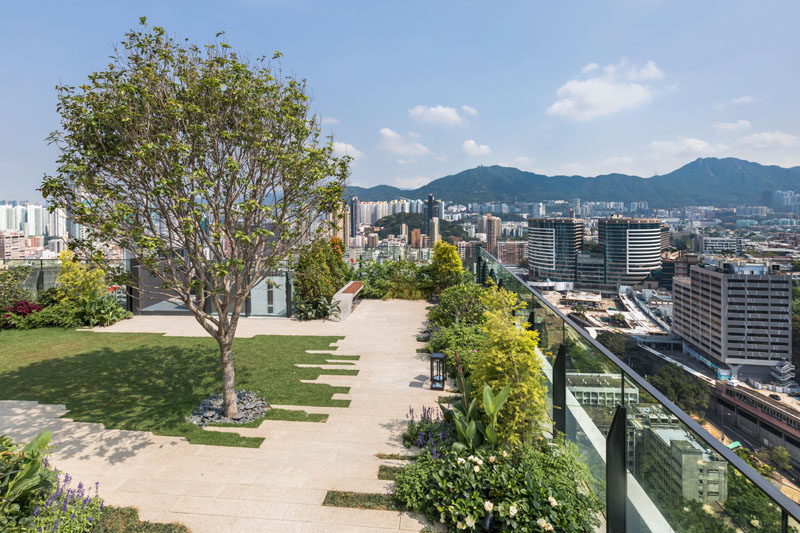 This modern residential building in Hong Kong has a rooftop park, complete with trees, a grassy area and benches.