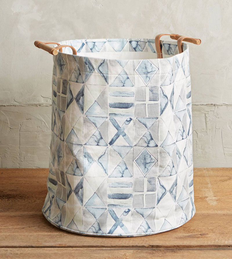 A unique blue and white water color pattern adorns this modern laundry hamper. With leather and wood handles, this cotton canvas hamper is gorgeous and sensible.