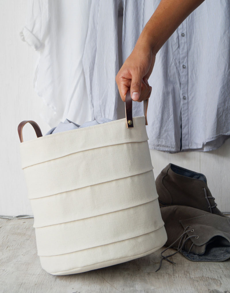 Delicate and light in an off-white color, this laundry basket has French seam detailing and brown leather handles. The exterior of the basket is made from 100% cotton canvas, with the lining made from 100% organic cotton.