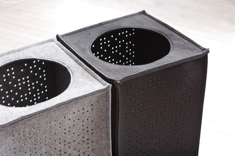 Made from polyester felt, these grey laundry hampers have cut out circular patterns.